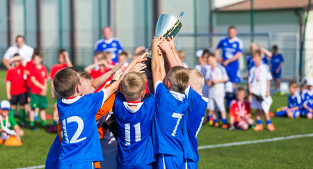 Photo for Young Soccer Players Holding Trophy. Boys Celebrating Soccer Football Championship. Winning team of sport tournament for kids children. - Royalty Free Image