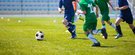 Foto de Boys play soccer match. Blue and green team on a sports field - Imagen libre de derechos