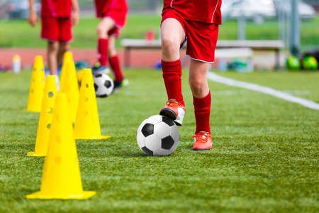 Photo for Soccer football players during the team training before the match. Exercises for football soccer youth team. Young player exercises with ball and marker cones - Royalty Free Image