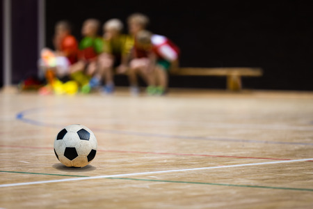 Photo pour Football Futsal Ball and Youth Team. Indoor Soccer Sports Hall. Children Indoor Soccer Team. Sport Futsal background. Indoor Soccer Winter League for Kids - image libre de droit