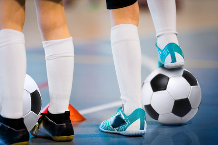 Foto de Indoor soccer players training with balls. Indoor soccer sports hall. Football futsal player, ball, futsal floor. Sports background. Futsal league. Indoor football players with classic soccer ball. - Imagen libre de derechos