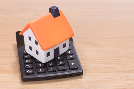 Photo for House miniature standing on calculator against wooden background - Royalty Free Image