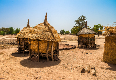 Foto de Traditional granaries made of woods and straw in an african village in Burkina Faso. They are on stilts to protect the crops against animals. - Imagen libre de derechos