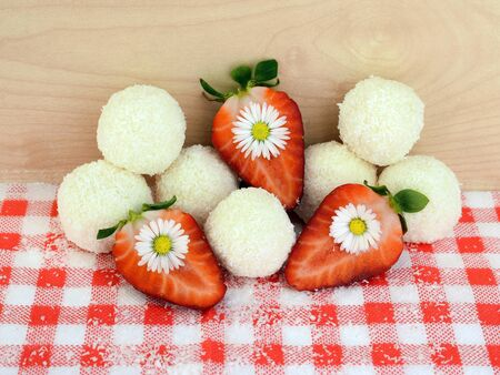 Foto de Romantic composition - homemade coconut balls, strawberries and daisy flowers. Everything you can eat - Imagen libre de derechos