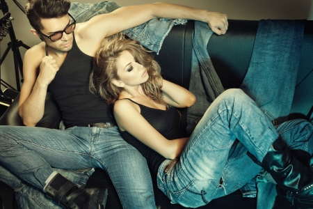 Photo pour Sexy man and woman dressed in jeans doing a fashion photo shoot in a professional studio  - image libre de droit