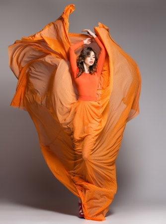 Photo pour beautiful woman in long orange dress posing dynamic in the studio - image libre de droit