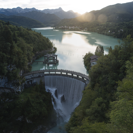Foto de Dam on the Barcis lake at sunset, with the village in the background. It was created in 1954 for the exploitation of hydroelectric power. - Imagen libre de derechos