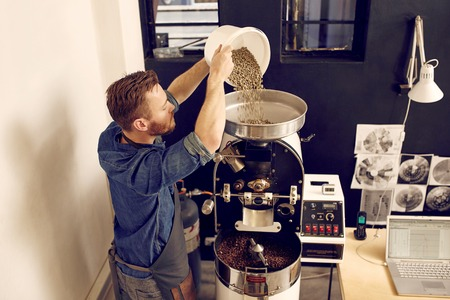Foto de High angle shot of a man pouring a batch of raw coffee beans into the top of a modern coffee roasting machine, with freshly roasted beans ready at the bottom - Imagen libre de derechos