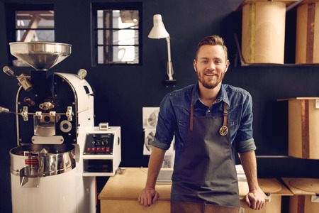 Foto de Portrait of a smiling man looking relaxed and confident in his workspace where he roasts coffee beans and distributes them - Imagen libre de derechos