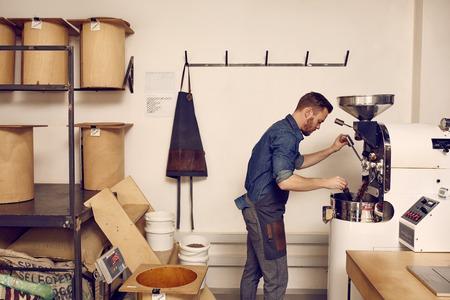 Foto de Male business owner in a clean workspace operating a modern machine for roasting coffee beans - Imagen libre de derechos