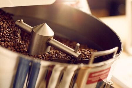 Foto de Aromatic coffee beans freshly roasted in a shiny and new modern appliance with clean metal parts in a roastery - Imagen libre de derechos