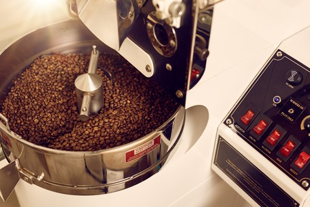 Foto de Modern appliance for roasting coffee beans looking shiny and new with a control panel with switches for various options of automated functions - Imagen libre de derechos