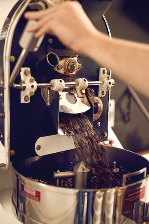 Foto de Cropped image of hands working a modern appliance that is dispensing the coffee beans it has freshly roasted into a shiny metal part below - Imagen libre de derechos