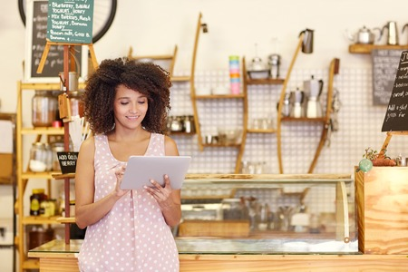 Photo pour Beautiful cafe owner running her small business with the help of a digital tablet while standing near the counter of her coffee shop - image libre de droit