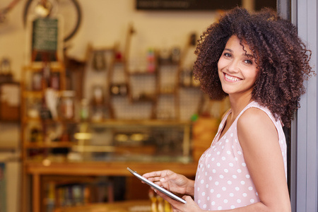 Foto de Beautiful mixed race woman with an afro hairstyle holding a digital tablet while standing in the doorway of her coffee shop - Imagen libre de derechos