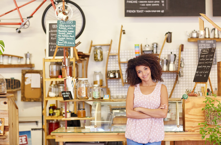 Young woman standing confidently in her coffee shop, proud of being a small business owner