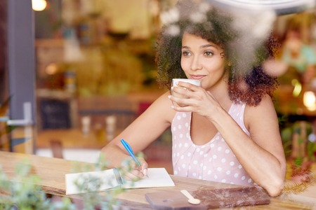 Photo pour Beautiful mixed race woman sitting in a coffee shop sipping her latte and daydreaming while gazing out of the window - image libre de droit