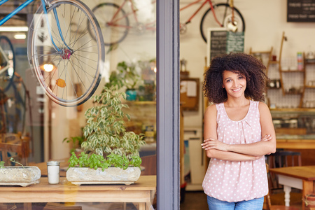 Photo for Young mixed race woman smiling, while standing in the door of her cafe with her arms folded proud to be the owner of a small business - Royalty Free Image