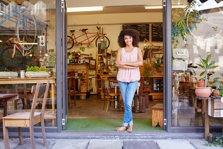 Foto de Full length shot of a young mixed race woman happily standing in the doorway of her trendy coffee shop - Imagen libre de derechos