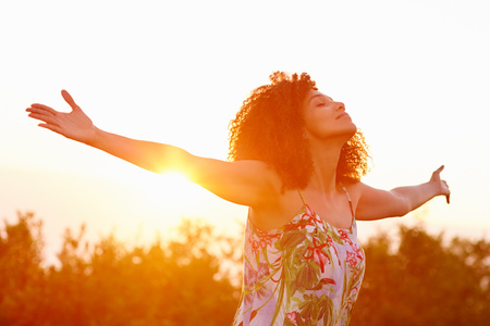 Foto de Beautiful mixed race woman expressing freedom on a summer evening outdoors with her arms outstretched - Imagen libre de derechos