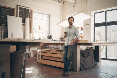 Photo pour Full length portrait of a young male designer standing comfortably in his naturally lit workshop, holding his morning cup of coffee and smiling at the camera - image libre de droit