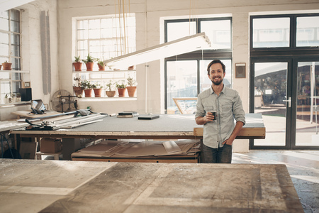 Photo pour Handsome entrpreneur craftsman standing confidently in his workshop studio smiling at the camera with his cup of coffee in hand - image libre de droit