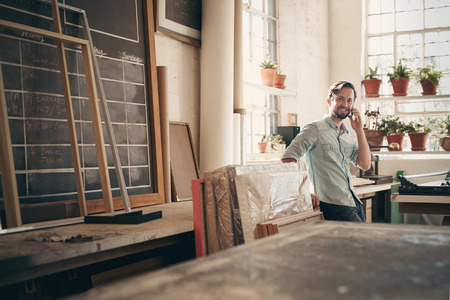 Photo pour Small business owner talking on his phone while smiling and standing casually in his studio workshop - image libre de droit