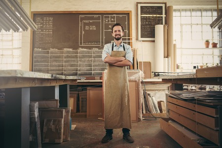Photo for Full length portrait of a desigern craftsman confidently standing with his arms crossed in his workshop and smiling at the camera - Royalty Free Image