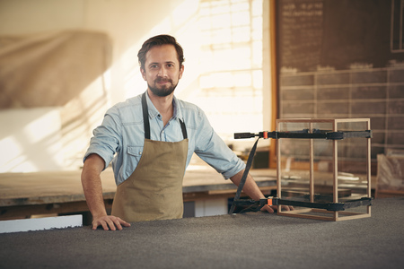 Photo pour Craftsman smiling at the camera while standing proudly in his workshop alongside a wood and glass display case that he is making with care - image libre de droit
