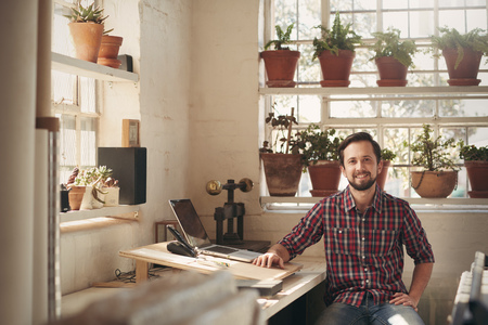 Foto de Young male designer sitting comfortably in his office space in his studio which has beautiful natural light and many plants - Imagen libre de derechos