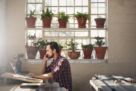 Foto de Young designer entrepreneur looking at his laptop while talking on his phone in his studio work space - Imagen libre de derechos