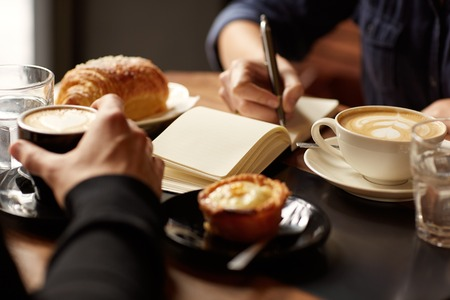 Foto de Cropped image of two people's hands at a table with coffees and pastry snacks - Imagen libre de derechos