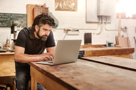 Photo for Bearded man who owns a small business, bending over at his work bench to type on his laptop, while working in his workshop and design studio - Royalty Free Image