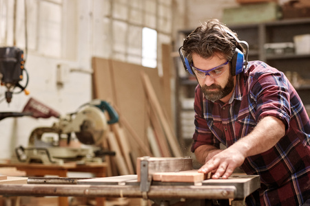 Foto de Skilled carpenter cutting a piece of wood in his woodwork workshop, using a circular saw, and wearing safety googles and earmuffs, with other machinery in the background - Imagen libre de derechos