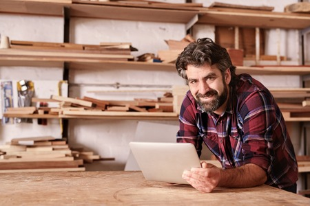 Photo pour Portrait of a small business owner smiling at the camera, resting on his workbench and holding a digital tablet, with shelves of wood behind him in his woodwork studio - image libre de droit