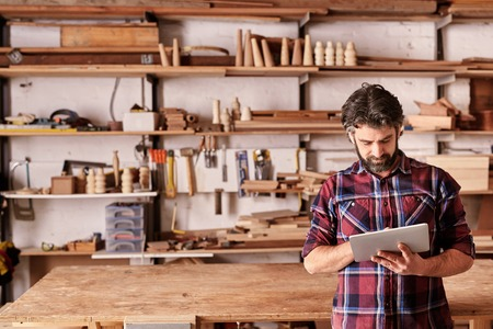 Photo pour Artisan woodwork studio with shelving holding pieces of wood, with a carpenter standing in his workshop using a digital tablet - image libre de droit