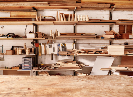 Photo pour Woodwork workshop wall with many shelves holding a variety of wooden pieces and planks of wood, and some hand tools, with a wooden work bench in the foreground - image libre de droit
