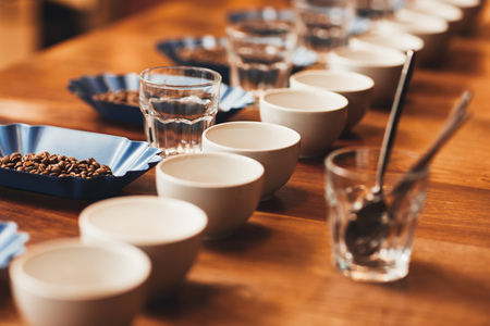 Foto de Neat row of cups and containers with fresh roasted coffee beans laid out on a wooden table ready for a tasting, with water glasses and teaspoons - Imagen libre de derechos