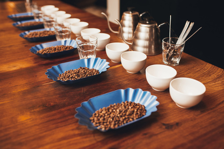 Foto de Wooden table top with neat rows of cups, water glasses and blue containers with roated coffee beans laid out in preparation for a professional coffee tasting - Imagen libre de derechos