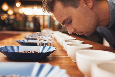 Foto de Casucasian man leaning over a wooden counter set with neat rows of containers with a variety of coffee beans, water glasses and coffee cups, smelling the fresh aroma of ground coffee - Imagen libre de derechos