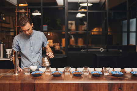 Foto de Professional barista in a modern roastery preparing for a coffee tasting session, at a wooden counter laid out with neat rows of cups, water glasses and open containers of coffee beans - Imagen libre de derechos