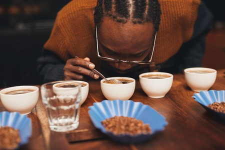 Foto de Croped shot of an African man bending down to smell the aroma of a cup of fresh coffee, that is part of a row of a variety of coffees on a wooden counter with roasted coffee beans - Imagen libre de derechos