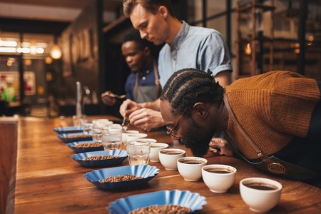 Foto de Modern roastery with three baristas training with a variety of roasted coffee beans and freshly made ground coffee at a wooden counter - Imagen libre de derechos