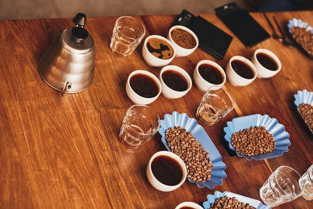 Foto de High angle view of a wooden table with many cups of coffee, fresh roasted beans in open continers, water glasses, a stainless steel kettle and digital scales ready for a coffee tasting - Imagen libre de derechos