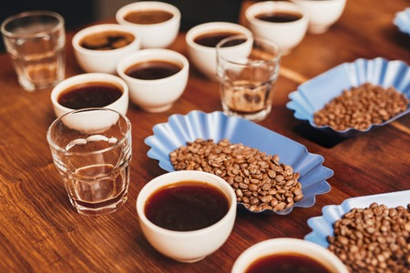 Foto de Many cups of coffee with open containers of freshly roasted coffee beans in a variety of flavours, and some water glasses on a wooden table for a tasting - Imagen libre de derechos