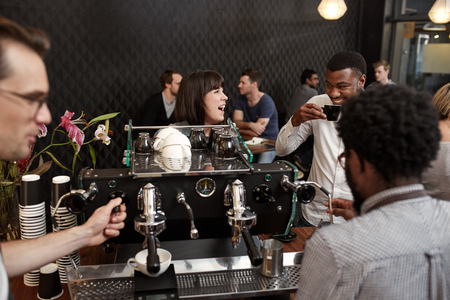 Photo pour Young woman laughing out loud while standing at the counter of a busy coffee shop, with her African guy friend, while baristas are making cappucinos at the coffee machine - image libre de droit