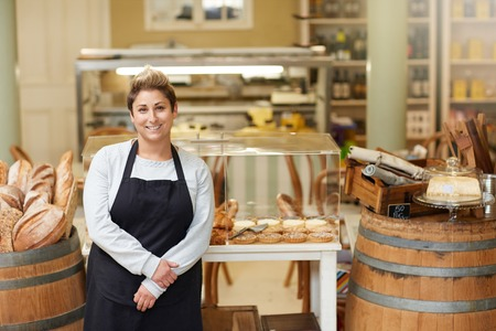 Photo pour A young deli employee standing in front of the pastry display - image libre de droit