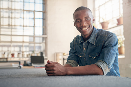 Photo pour Low angle portrait of a handsome young African small business owner sitting at a work bench in his beautifully lit workshop, smiling at the camera confidently - image libre de droit
