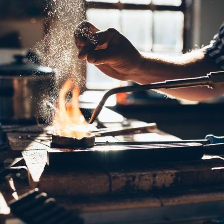 Foto de Closeup of a jeweler using a torch to melt metal in a crucible while working in his jewelry design studio - Imagen libre de derechos