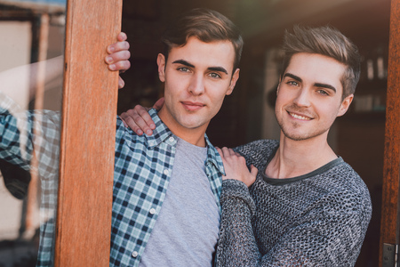 Photo pour Portrait of a smiling young gay couple standing welcomingly at the door to their apartment - image libre de droit
